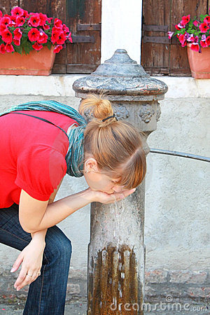Girl drinking cold water from water pump
