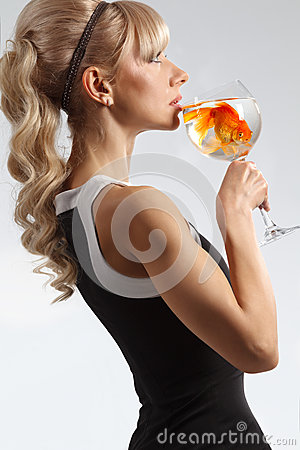 Girl drinking glass of water with golden fish