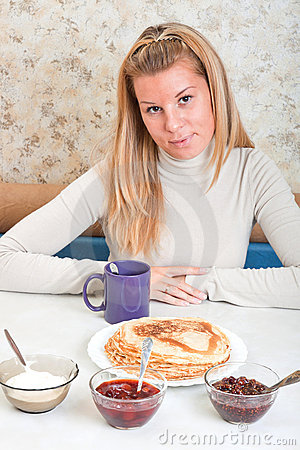 Girl drinks tea and eats russian pancakes