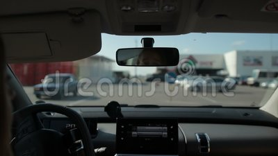 Girl driving car on parking lot near shopping mall stock video footage