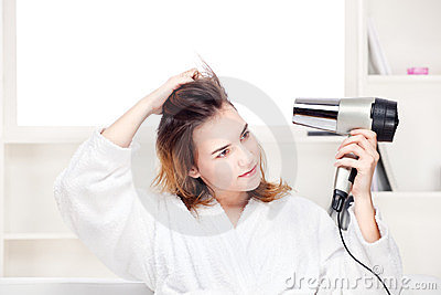 Girl drying her hair at home
