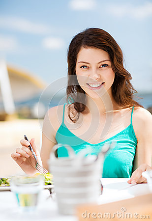 Girl eating in cafe on the beach