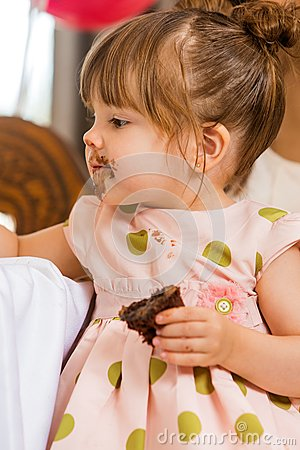 Girl Eating Cake With Icing On Her Face