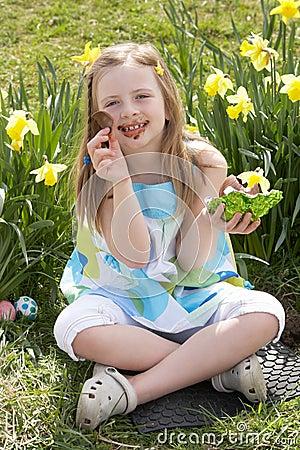 Girl Eating Chocolate Egg On Easter Egg Hunt