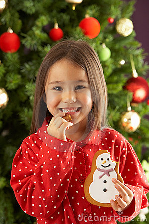 Girl Eating Cookie In Front Of Christmas Tree