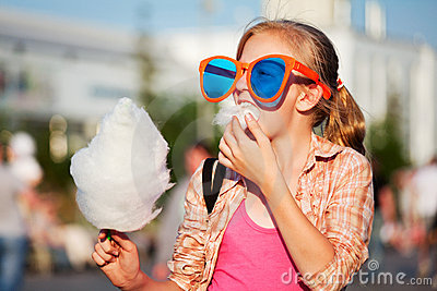 Teen girl eating cotton candy on the city street