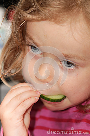 Girl eating cucumber