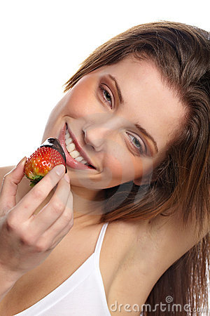 Girl eating a fresh red strawberry