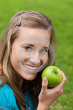 Girl eating a green apple in a park
