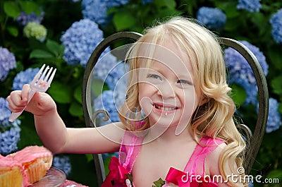 Girl eating pink cupcakes