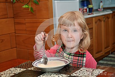 Girl is eating porridge