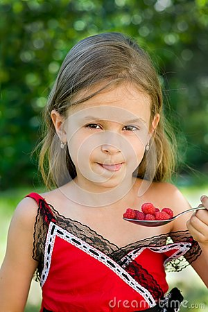 Girl eating raspberry