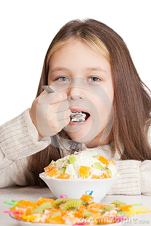 Girl eats fruit dessert spoon while sitting at a table