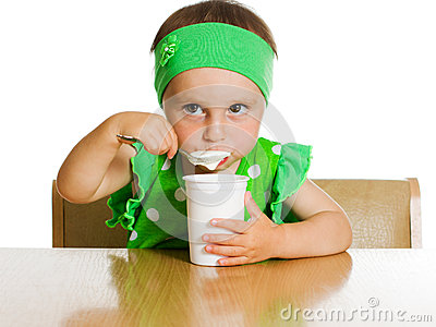 Girl eats with a spoon dairy product.