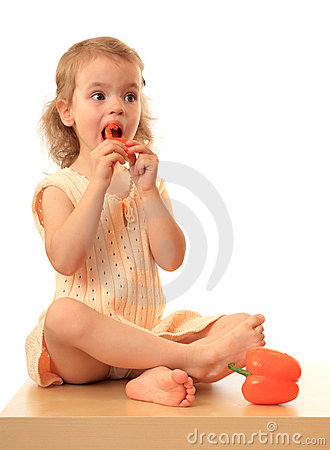 Girl eats a sweet pepper.