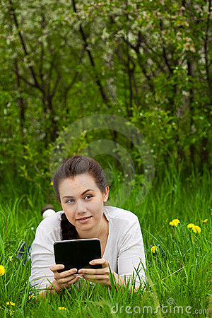 Girl with ebook lying on the grass