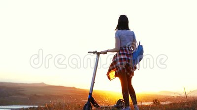 Girl with an electric scooter stands with her back and looks at the sunset,slow mo. Girl with a backpack with an electric scooter stands with her back and looks stock video footage