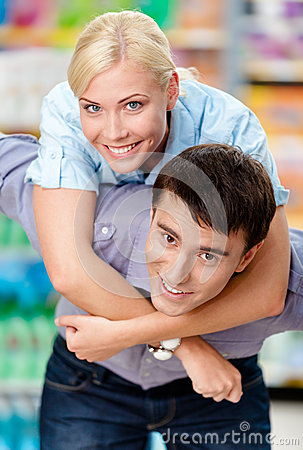 Girl embraces man in the supermarket