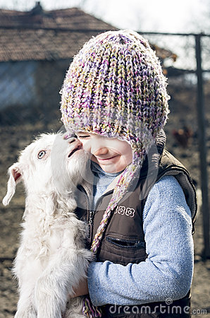 Free Girl Embracing A Goatling. Stock Image - 27927411