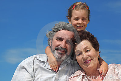 Girl embracing grandparents from back and smiling