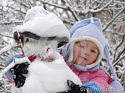A girl embracing a snowman