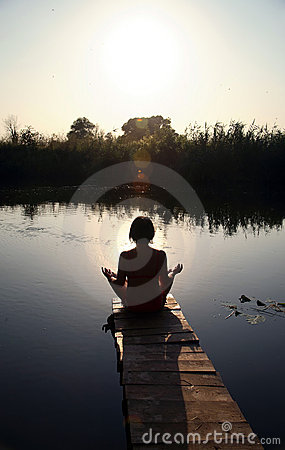 Girl is engaged in meditation on the small bridge