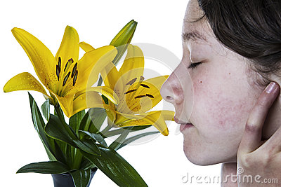 Girl enjoying the smell of a flower in full bloom