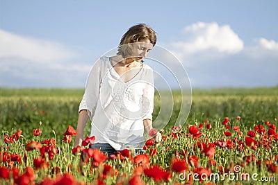 Girl enjoying summer in a poppy field