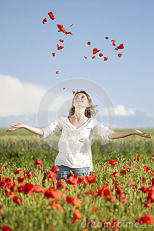 Girl enjoying summer in a poppy field