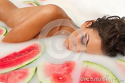 Girl enjoys a bath with milk and watermelon.