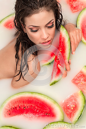 Girl enjoys a bath with milk and watermelon.