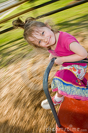 Girl enjoys merry-go-round ride
