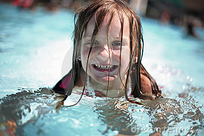 Girl enjoys summer day at the swimming pool.