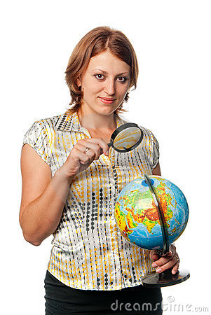 Girl examines the globe through a magnifier