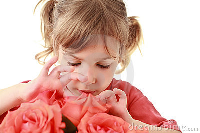 Girl examines and touches petals of rose