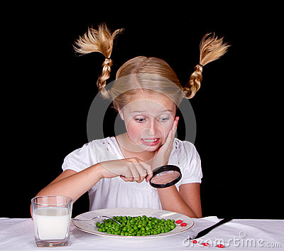 Girl examining bugs on table with magnifying glass