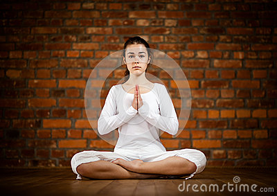 Girl exercising yoga against brick wall