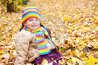 Girl on fall autumn leaves in park Stock Photo