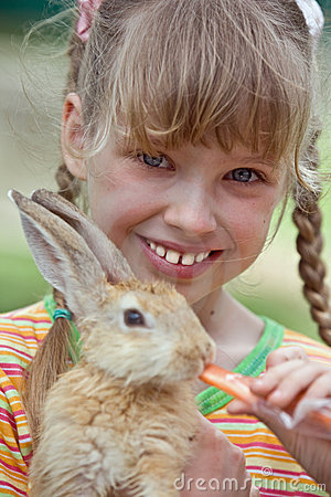 Girl feed  rabbit with  carrot.