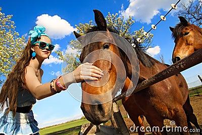 Girl feeding her horses