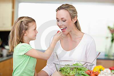 Girl feeding her mother with tomato
