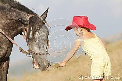 Girl feeding a horse on farm outdoors