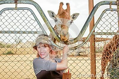 Woman feeding giraffe
