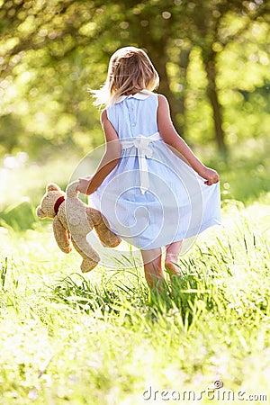 Girl In Field Carrying Teddy Bear