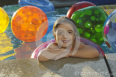 Girl With Floating Ring And Beach Balls In Swimming Pool