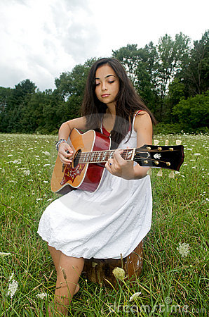 Girl in flower field playing a guitar