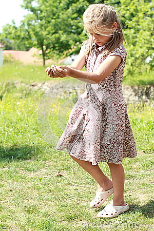 Girl in flowered dress carrying ground