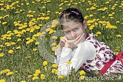 Girl in the flowering meadow looking at camera