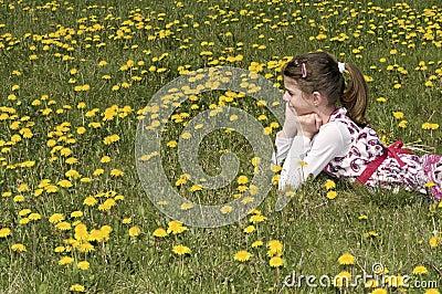 Girl in the flowering meadow looking far