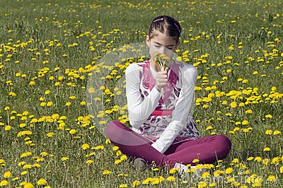 Girl in the flowering meadow smelling